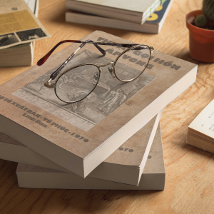 three books mockup lying on top of each other and round glasses a17407