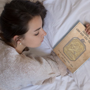 young girl holding a book on her hand while lying down on her bed mockup a14275